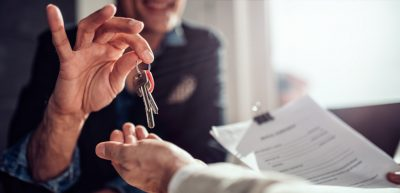 A male home owner turning over the key of his house to a real estate agent being his trusted guide to selling his house.
