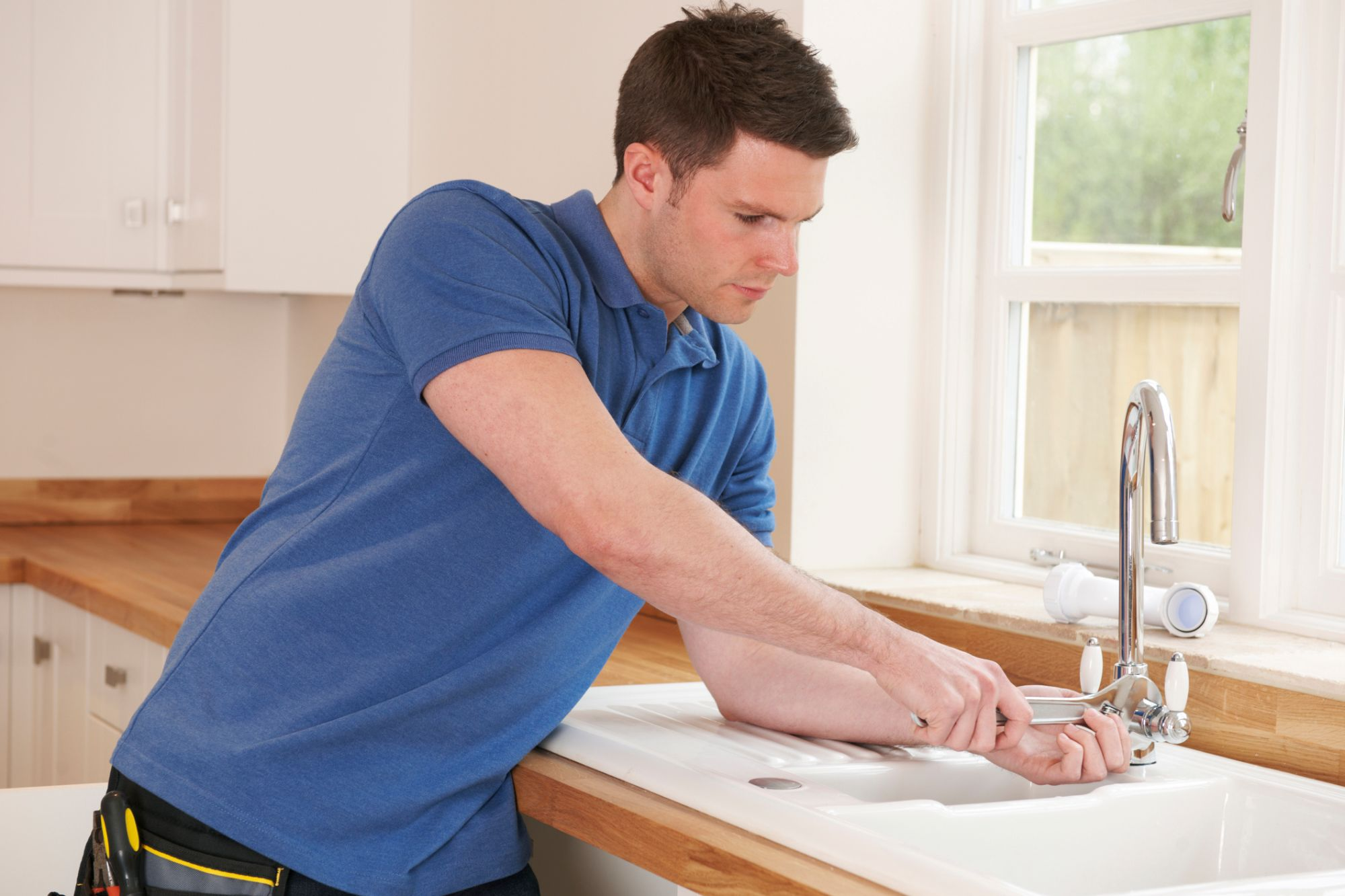 Man fixing the kitchen faucet